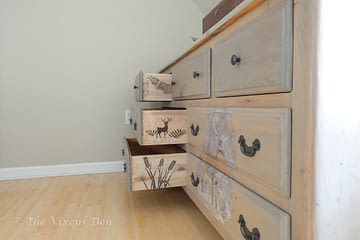 dresser stained to look like raw wood with DIY transfer and stenciled drawer sides